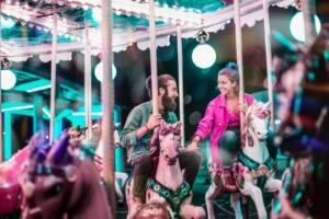 Man and woman riding a carousal