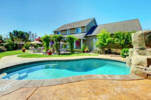 homeguide-backyard-concrete-pool-with-steps-and-rock-landscaping